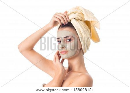 cutie Young girl takes care her skin with cleansing mask on face and towel on head isolated on white background. Health care concept. Body care concept. Young woman with healthy skin.
