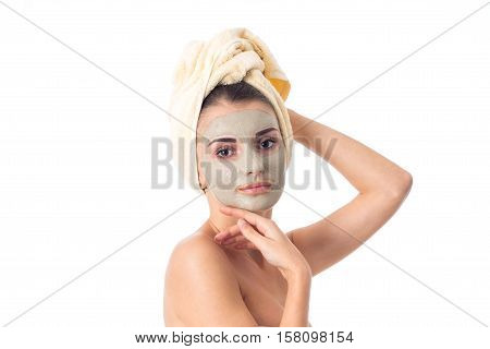 Young beauty girl takes care her skin with cleansing mask on face and towel on head isolated on white background. Health care concept. Body care concept. Young woman with healthy skin.