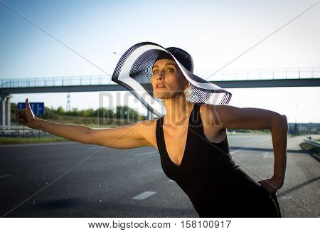 Pretty woman wearing big hat on road hitchhiking concept