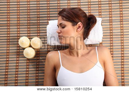 Woman lying on bamboo mat sleeping