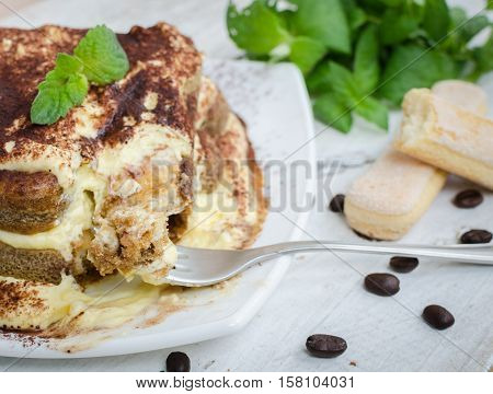 Tiramisu traditional Italian creme dessert with mint leaves and coffee beans on white wooden background. Tiramisu cake. Homemade tiramisu dessert close-up. Italian cuisine concept. Selective focus.
