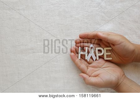 HOPE and white ribbon on hands Bone cancer awareness Multiple Hereditary Exostoses Postpartum Depression