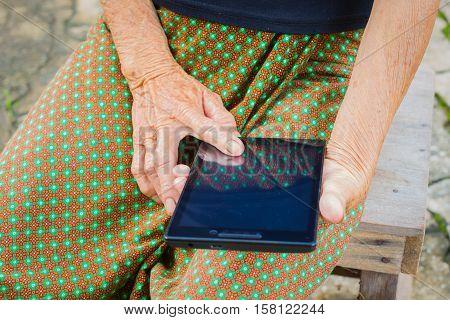 horizontal photo of closeup asian elder woman using tablet technology concept.