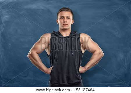 Muscular young man in sportswear standing on the dark blue background. Sport and healthy lifestyle. Keep fit. Athletic body.