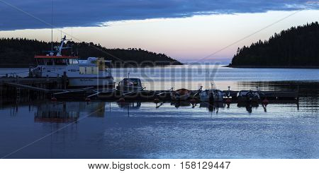HIGH COAST HERITAGE, SWEDEN ON SEPTEMBER 04. View of the early morning lit in a small harbor on September 04, 2016 in Barsta, Sweden. Bridge and boats. Dawn. Editorial use.