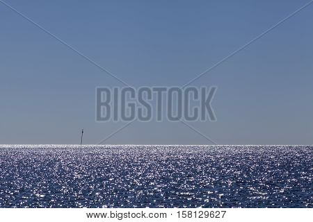 Sea, ocean and a navigation mark, buoy beacon in backlight. Glittering, calm view.