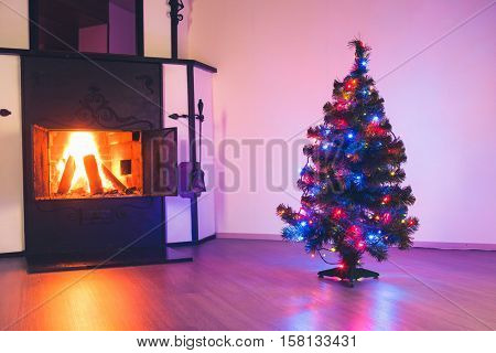 Christmas tree with lights garland and fireplace