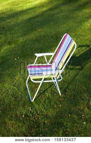 garden chair on green lawn background