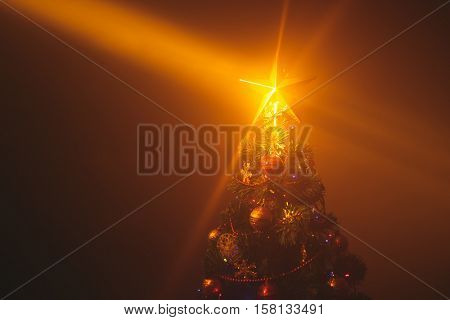 Christmas tree with shining star and dense mist