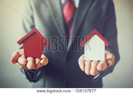 Businessman Holding Two Houses And Can Not Decide Choosing The Right House