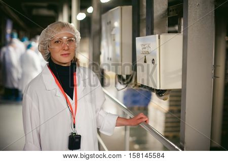 Worker Standing Near Electrical Shield. A Woman In A White Robe And Goggles, Is Holding On To The Ra