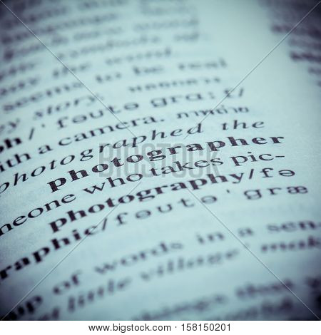 Close Up Of Old English Dictionary Page With Word Photographer. Shallow Depth Of Field And Toned Pag