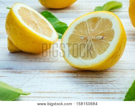 Closeup Fresh Lemons And  Lemons Leaves On Shabby Wooden Background. Fresh Lemons And Lemon Slice On