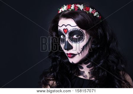 Close Up Of Young Woman With Skull Make Up And Flowers In Hair