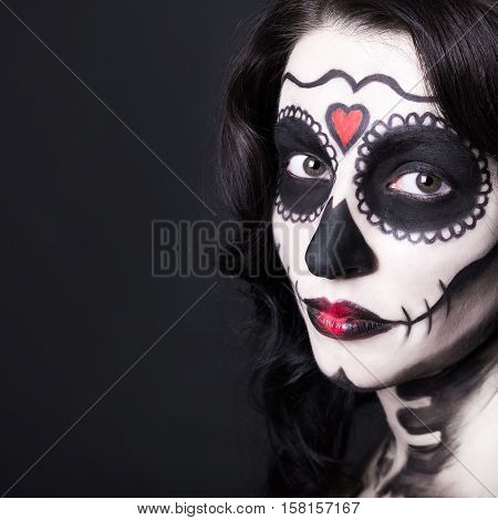 Close Up Portrait Of Beautiful Woman With Creative Sugar Skull Make Up Over Black