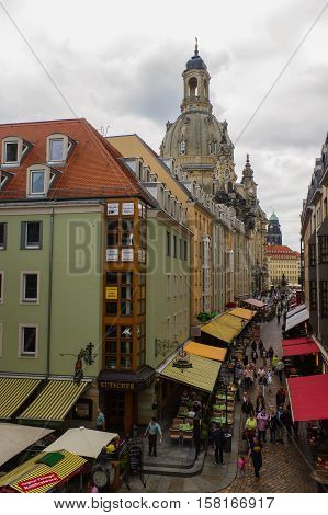 DRESDEN GERMANY - SEPTEMBER 21 2013: the Pedestrians in the Munzgasse alleyway. The historic cobblestone alley is lined with many of Dresdens most famous restaurants and cafes.