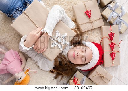 Happy excited girl child in santa hat lay on warm carpet among Christmas gift boxes. Xmas holiday concept. Top view of excited beautiful female kid got lots of presents