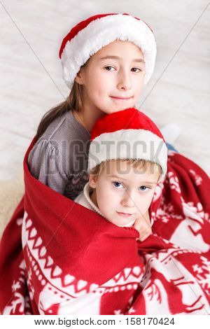 Adorable children in santa hats closeup portrait. Kids wait for winter holiday gifts. Boy and girl, brother and sister sit wrapped up in christmas blanket