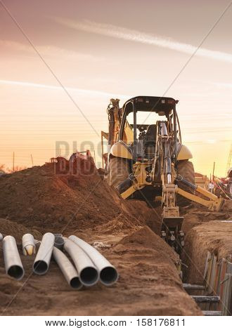 Bulldozer carving hole for pipe laying on constructions site.   End of work day sunset.
