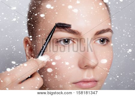 winter christmas people beauty concept- young brunette with short hair woman make-up. girl Cosmetic. correction and eyebrow styling. perfect eyebrows. over snow background