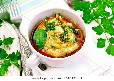 Fish baked in tomato in Zandvoort in white bowl on a napkin, parsley on the background light wooden boards
