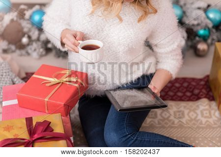 Being informed. Nice young blond woman holding a tablet and having tea while reading news