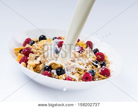 Pouring Milk in a Bowl of Cornflakes, Blueberries and Raspberries