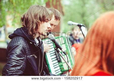 Big public market day in town. Singer and musician performing as street musician