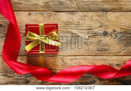 holiday red gift box with golden tape scarlet silk ribbon on the old wooden table