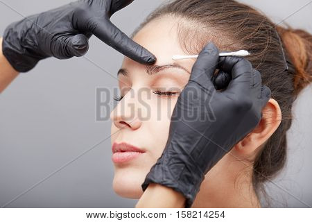 Cosmetologist making permanent makeup on lips and eyebrows