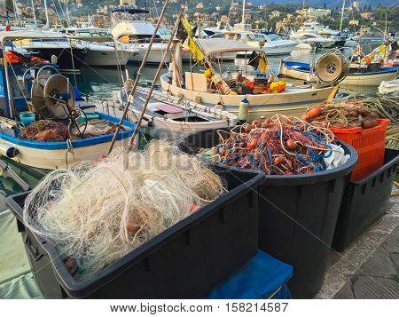 Plastic box full of fishing net, floats, nylon rope used in fishing industry in evening at Tigullio Gulf of Santa Margherita Ligure, Italy