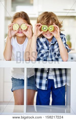Boy and girl hiding behind fruits in the kitchen