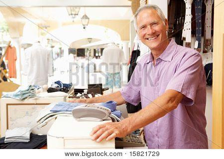Asistente de ventas masculino al finalizar la compra de la tienda de ropa