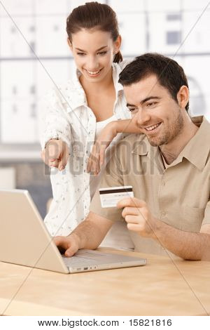 Happy couple using laptop, shopping online at home, using credit card, having fun.