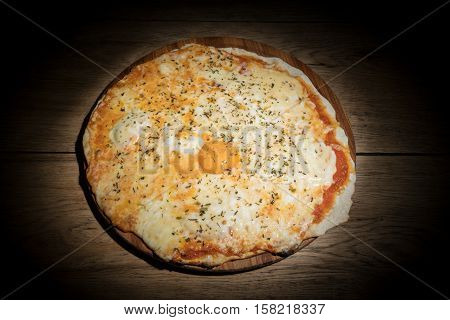 Cheese Italian pizza with a whole egg yolk in the middle served on a wooden plate in dark