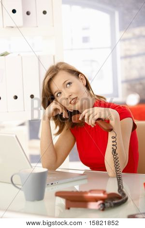 Young businesswoman sitting at office desk, holding phone, thinking.