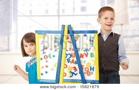 Portrait of happy kids playing together with drawing board, looking at camera, smiling.