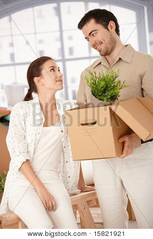Happy young couple moving to new house, unpacking boxes, smiling at each other.?