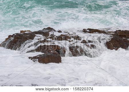 Waves crashing over the rock with white foam
