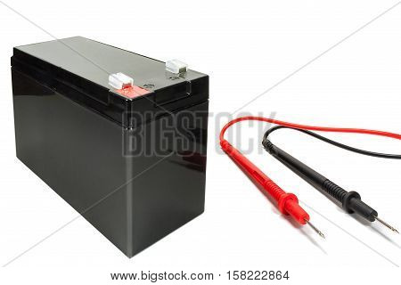 Backup battery with mutimeter probe on a white background