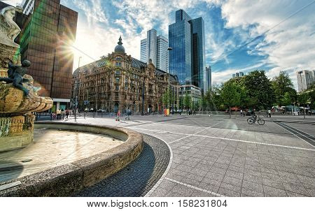 Frankfurt am Main Germany - April 29 2012: With special sun flare. Architecture of Untermainanlage street with skyscrapers in the business center of Frankfurt am Main. People on the background.