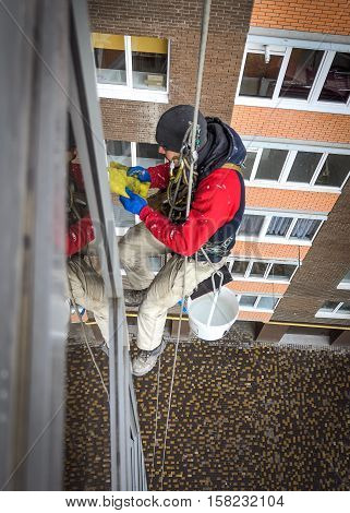 window cleaner hanging on a rope and wash the glass