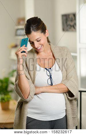 Blissful pensive pregnant woman using smartphone at home. Entrepreneur job success during pregnancy.
