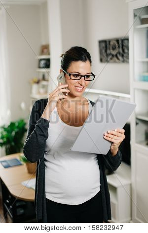 Successful pregnant woman working at home making a cellphone business call and using digital tablet pc. Female entrepreneur doing her job during pregnancy.