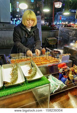 Seoul South Korea - March 14 2016: Female seller of langoustines at Myeongdong open street market in Seoul South Korea. Selective focus