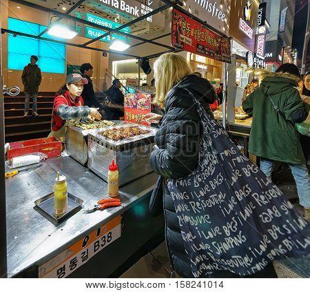 Girl Buying Street Food In Myeongdong Street Market Seoul