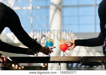 Three female hands taking alcohol cocktails. Sunlight. Golden bracelet.
