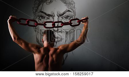One young man in a black chain raises above his head. The concept of freedom, or sports. Free spase for comercial Grey background with copy space