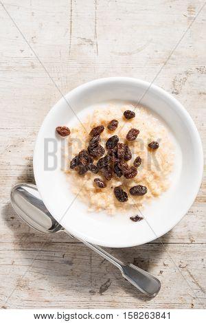 Bowl Of Porridge Oats And Raisins On White Wooden Background