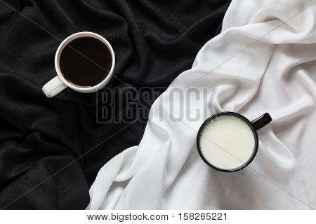2 cups of coffee and milk on the black and white fabric. Top view